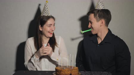 chifre : Pretty girl and man celebrates a holiday, sits at a table with a cake and a candles playing with party blowers, 4k