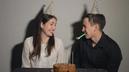 chifre : Smiling couple celebrates a holiday playing with party blowers, slow motion Vídeos