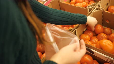 seçme : young girl in a supermarket selects the tomatoes, close up Stok Video