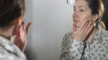 rejuvenescimento : The portrait of young woman with skin applying a cream on her face.