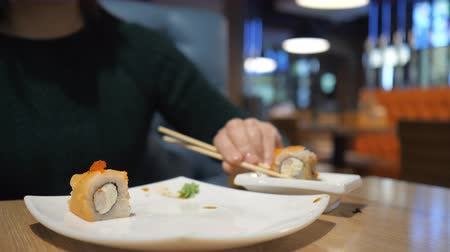 pessoa irreconhecível : The concept of Japanese and Chinese cuisine. The unknown girl in the restaurant has wooden chopsticks sushi and rolls.
