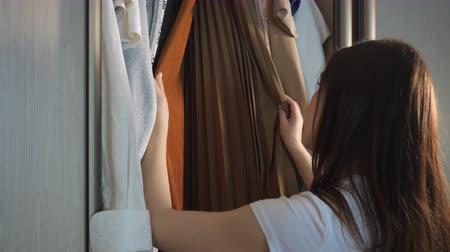 roupas : Young woman choosing clothes in wardrobe at home before a party close up