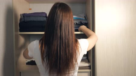 get out : A woman is tidying up the closet. Young girl put clothing wool sweater with wardrobe Stock Footage
