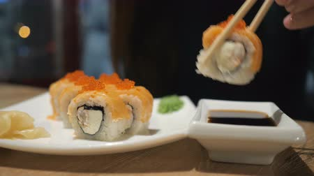 rýže : The concept of Japanese and Chinese cuisine. The girl in the restaurant has wooden chopsticks sushi and rolls.