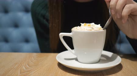 viennese : girl with a spoon tries foam with cappuccino. Stock Footage