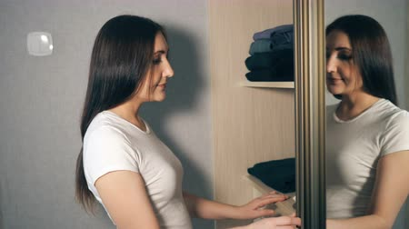 szobalány : girl takes out clothing wool sweater with wardrobe. Stock mozgókép