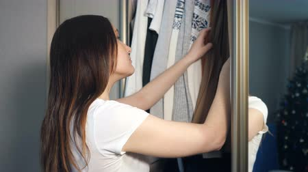 decidir : Young woman choosing clothes in wardrobe at home.