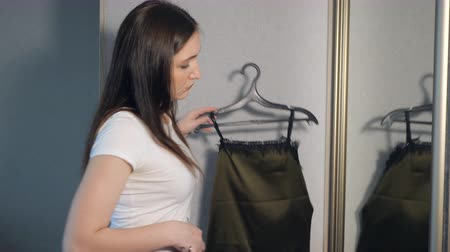 traje de passeio : pretty girl in front of the mirror trying on clothes before a walk. Stock Footage