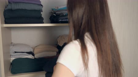 drawer : Housewife organizing clothes in wardrobe. Young girl put clothing wool sweater with wardrobe, back view Stock Footage