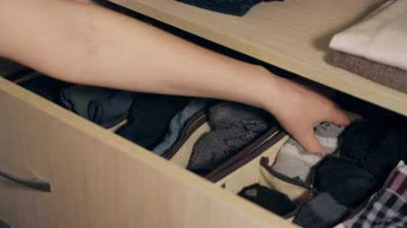 interior : The drawer with underwear in the closet. Housewife organizing clothes in wardrobe, slow motion