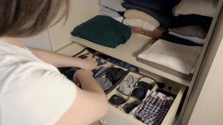 носок : The drawer with underwear in the closet, slow motion. Housewife organizing clothes in wardrobe, close up.