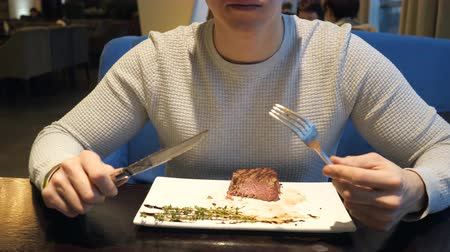 garfos : nameless man eating steak with fork and knife in fast food cafe at evening, slow motion