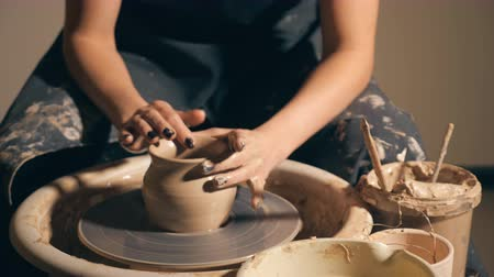 hrnčíř : Woman girl her hands dub wall jug, sculpts out of clay on circle. Dirty hands in the clay. slow motion.