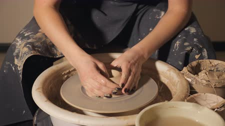 hrnčíř : ceramic workshop - the girl makes a pot of clay on a potters wheel. hands closeup