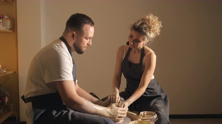 clay pot : Young couple enjoying working with clay at the pottery workshop, slow motion Stock Footage