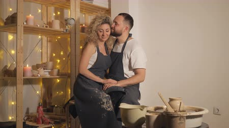 clay pot : happy family on a creative joint vacation. romantic couple sitting and kissing in workshop.