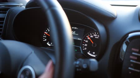kilometer : woman drives a car - closeup of hand on the steering wheel and speedometer