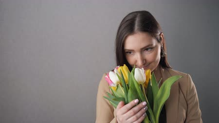 букет : Beautiful girl with a bouquet of tulips, enjoy and looking out the window. copy space