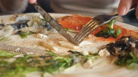 omega : woman eating leftovers fish with knife and fork in cafe, close up. 4k Stock Footage