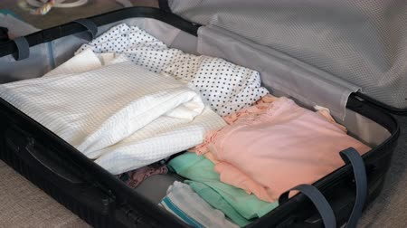 csomagolt : Woman packing travel suitcase at home, close up