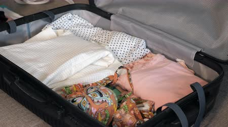 чемодан : Woman packing travel suitcase at home, close up