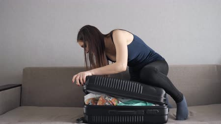 chock : Woman standing on overfilled suitcase and trying to close. Stock Footage
