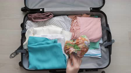 чемодан : A young woman puts things in a suitcase. The concept of travel and trip Стоковые видеозаписи