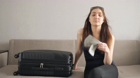 csomagolt : girl with suitcase sits on the couch and waving dollars. waiting for vacation Stock mozgókép