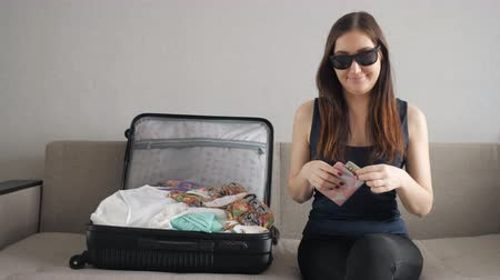 pas : girl in sunglasses sits on the couch and waving dollars. waiting for vacation