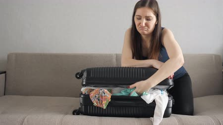 chock : girl casually packing and trying to close a crowded suitcase. concept of long-awaited vacation, close-up. Stock Footage