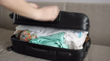 chock : woman trying to close overflow suitcase close up