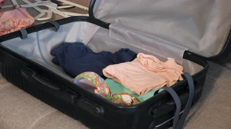 csomagolt : girl packing travel suitcase at home, close up