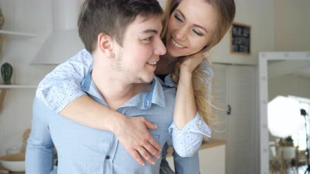 jumped : blond girl jumped on guy shoulders from back laughing starts kissing man holds woman in arms against kitchen close view