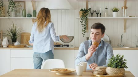 клецка : blond girl serves breakfast putting biscuits and cups on table and dumplings on plate kisses guy in kitchen Стоковые видеозаписи