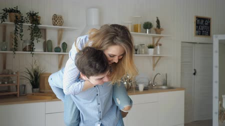 jumped : girl jumped on guy shoulders from back laughing starts kissing man holds woman in arms against kitchen close view slow motion