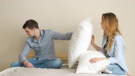 take offense : attractive blond long haired girl asks guy to play with pillows sitting on bed but man refuses in bedroom 4k Stock Footage