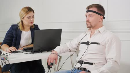 kihallgatás : polygraph technician reads questions from a laptop. man connected to the lie detector circuit.
