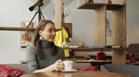 chatter : Young woman is meeting in the cafe for two friends drinking a cup of coffee. Three girlfriends are meeting in cafe. Front view. Stock Footage