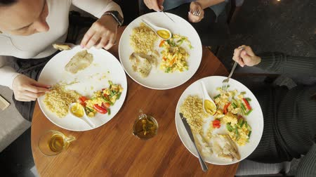 столовые приборы : Three women friends are eating their food in cafe. Plates on the table top view. Hands close-up. slow motion
