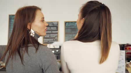 решить : Two women discuss the menu and choose food in a cafe standing at the bar counter. back view.