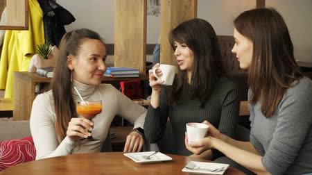 dedikodu : Three girlfriends are meeting in cafe. Drinking beverages and talking each other. Front view. Stok Video