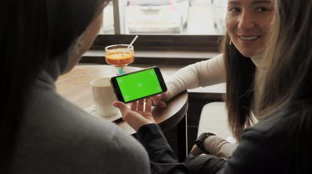 chatter : Women girlfriends are looking at green screen in smartphone and talking about it sitting in cafe. Friendly meeting in the cafe. Stock Footage
