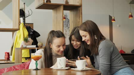 chatter : Three woman girlfriends are looking something in smartphone and talking about it sitting in cafe. Front view. Stock Footage