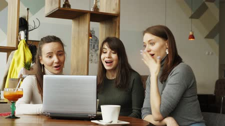 удачливый : slow motion of successful women team in coworking center: reading a message with good news in laptop