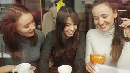 chatter : Women girlfriends in a cafe. Front view from behind glass. Stock Footage