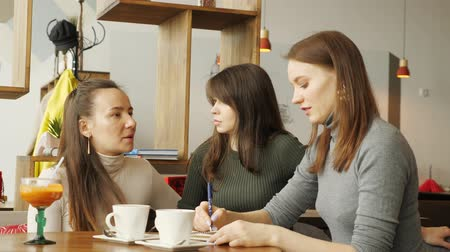 make friends : Colleagues women discuss joint project in cafe in the coworking center and making notes in a notebook. Front view. Stock Footage