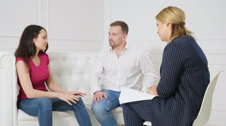 psychotherapist : Unhappy couple sharing emotions with psychologist.
