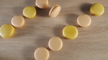 işlenmiş : Yellow and beige macaroons on wood background, one cookie rolls across the table. view from above