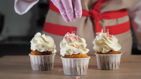 borrifar : Pastry chef sprinkles muffins with cream in paper cups with pink chocolate crumb. Hand close-up. Stock Footage