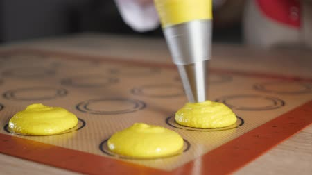 acıbadem kurabiyesi : Pastry chef is pouring dough from pastry bag on stencil silicone mat on the table. Cooking macaroons, close-up. selective focus Stok Video